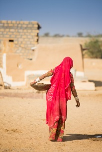 Rajasthani woman wearing a red sari walking through her village with a metal tray for collecting grains.