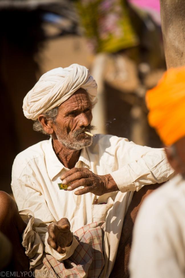 Rajasthani men wearing turbans sporting serious mustache and smoking bidis in Thar desert, India.