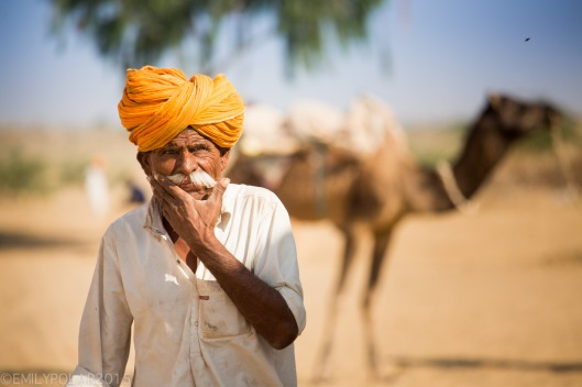 Rajasthani man with orange turban massages his white mustache with deep thoughts while walking in dusty Thar desert village.