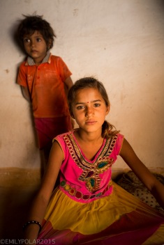 Young woman sitting on the dirt floor of her home in a small village in the Thar desert, India.