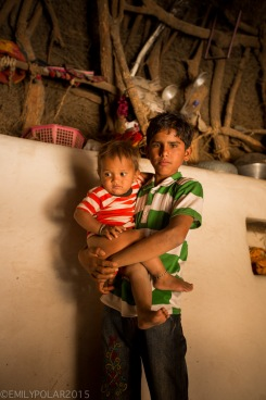 Big brother holding his baby brother in his families mud home in a rual village of the Thar desert.