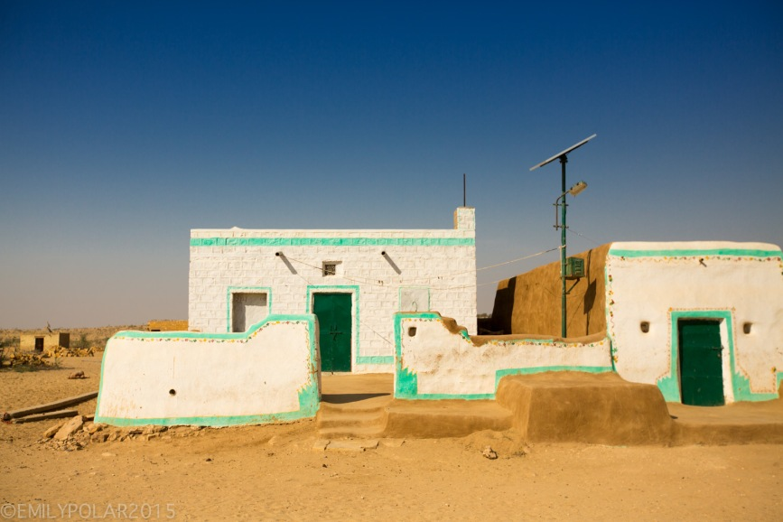 Cute mud home painted white with green door and trim in a small village of the Thar desert in Rajasthan.