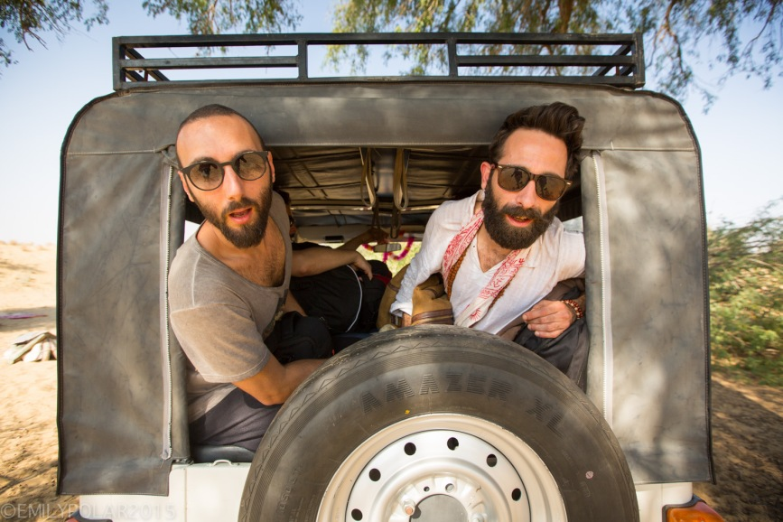 Italian friends looking out of the back window of a jeep on a desert safari in Rajasthan.