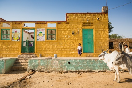 Young boy stands outside of mud home in a small desert village in Thar Desert.