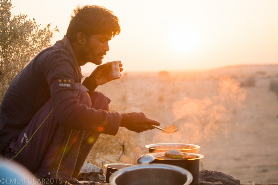 Rajastani man cooking breakfast over a campfire in the desert of Jaisalmer.