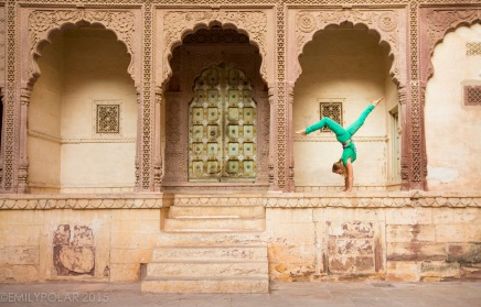 Woman doing handstands in golden arches at Mehrangarh Fort in Jodhpur.