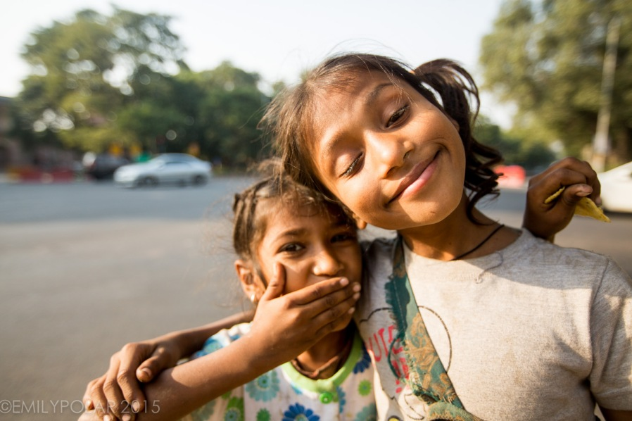 Young Indian girls make cute faces at the camera asking for money in the streets of Delhi, India.
