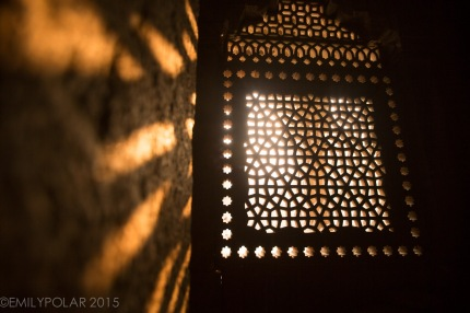 Beautiful carved marble windows with light shinning through making shadows on the walls of Humayuns Tomb, Delhi, India.