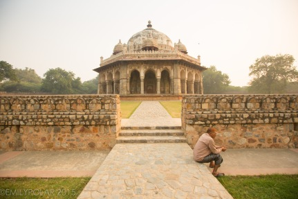 Indian man sitting on a stone path taking a break from tourism at Humayuns Tomb, Delhi, India.