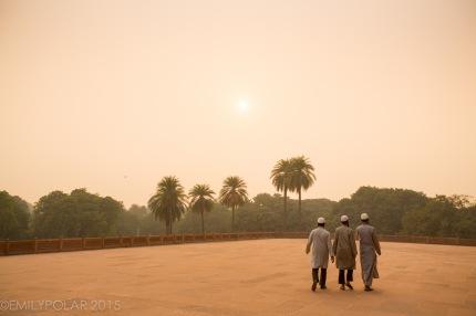 Three muslim men walking around Humayuns Tomb at sunset.
