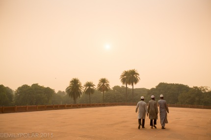 Three muslim men walking around Humayuns Tomb at sunset.