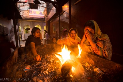 Hindu men and women holding hands over holy fire and smoke for prayer at Kalka Mandir Temple in Delhi.