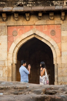 Young Indian couple taking a picture with smart phone at Sheesh Gumbad in Lodi Gardens Delhi.
