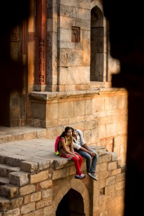 Cute young Indian couple sitting at Sheesh Gumbad Mosque in Lodi Gardens, Delhi.