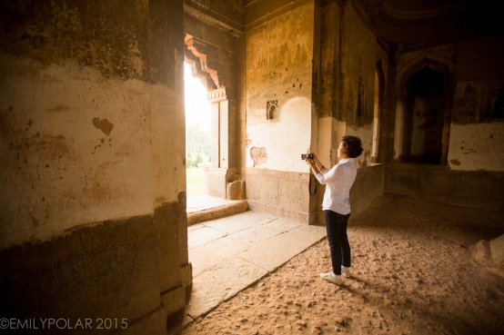 Asian woman taking a photo from inside a temple at Lodi Gardens, Delhi.