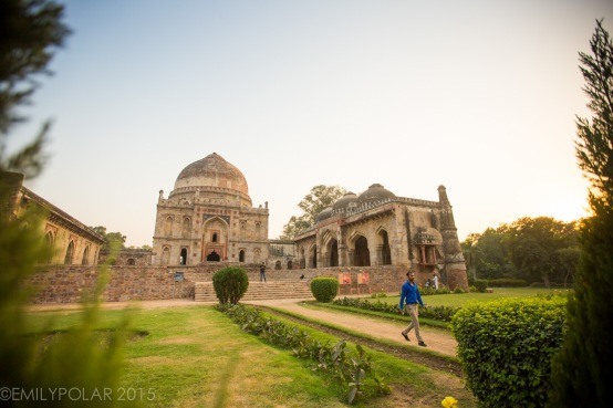 Indian tourist walking along the dirt path through green lawns and trees near Bara Gumbad tomb and mosque at Lodi Gardens, Delhi.