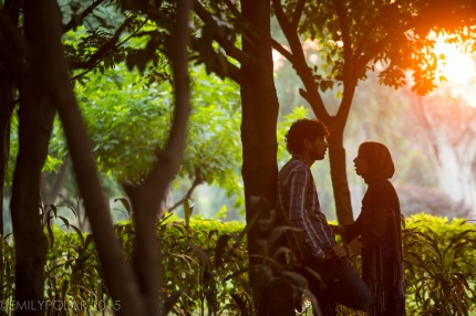 Young Indian couple talking in the forest lit by the glowing setting sun at Lodi Gardens, Delhi.