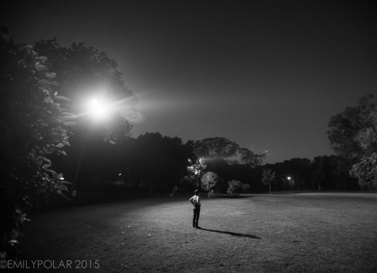 Tourists walk on the grounds of Lodi Gardens at night lit my a street light in Delhi, India.