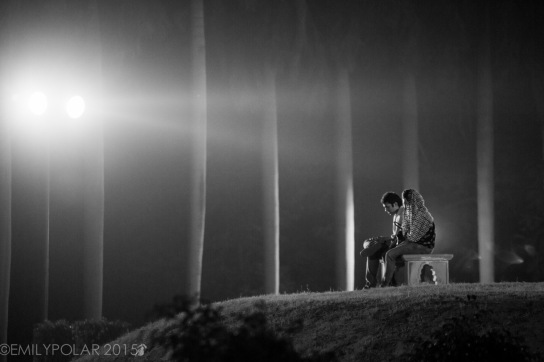 Young Indian couple sitting on a bench in Lodi Gardens at night in Delhi, India.
