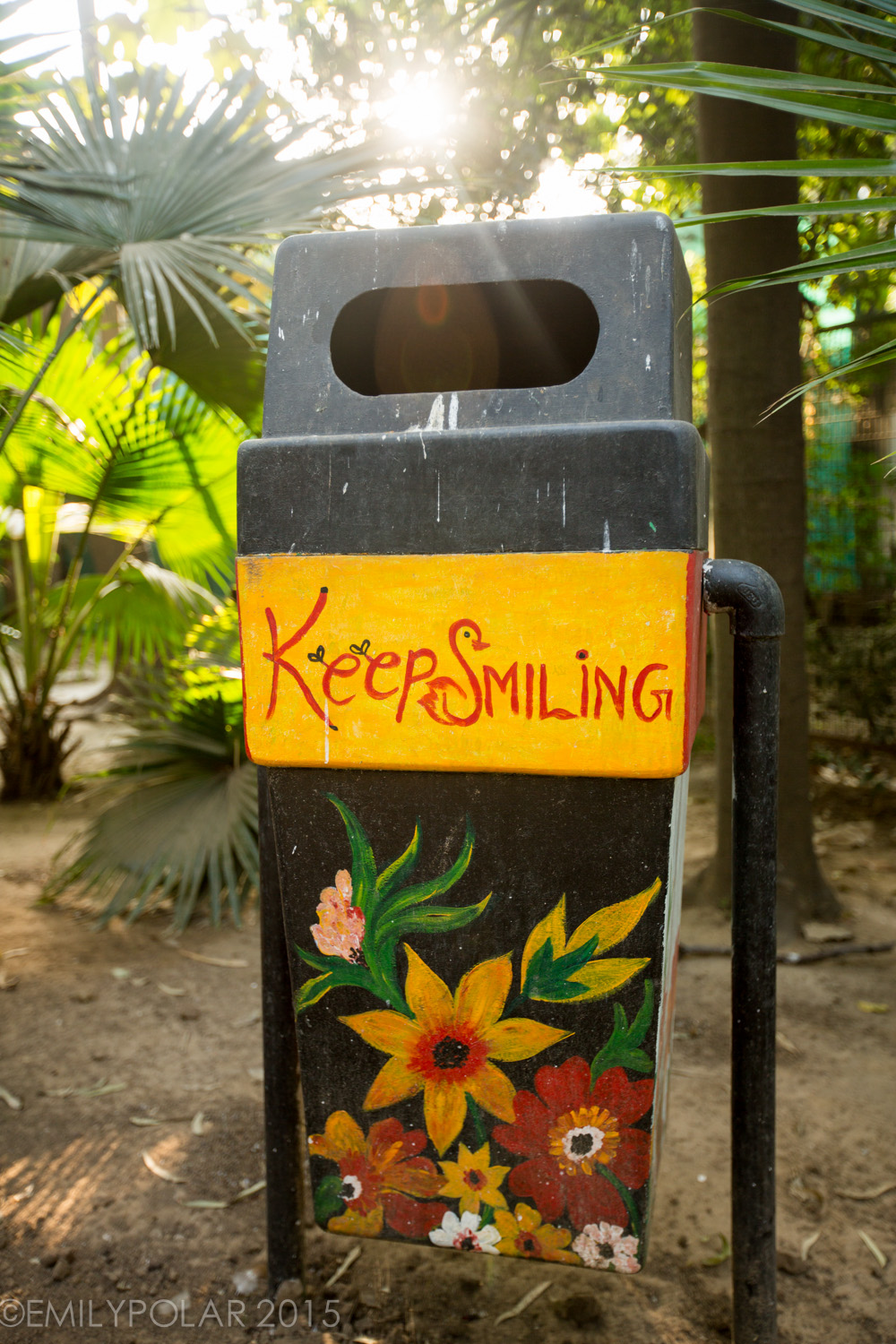 Trash can with painted flowers and keep smiling note on it in Lodi Gardens, Delhi.