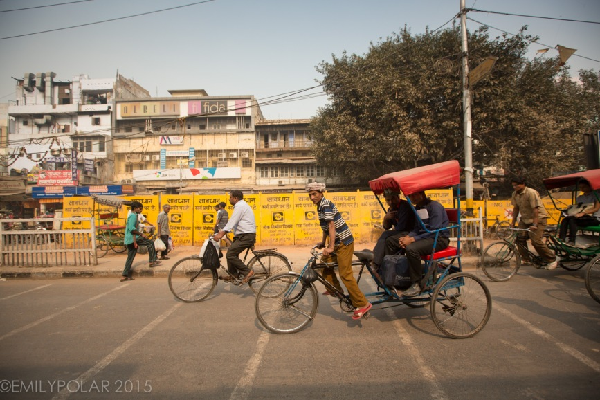 Busy streets of Old Delhi with rickshaws, bicycles and people walking.