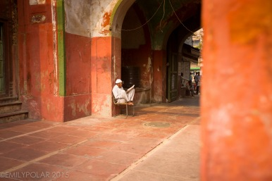 Old Muslim man reading in a chair at an orange mosque in Old Delhi, India.