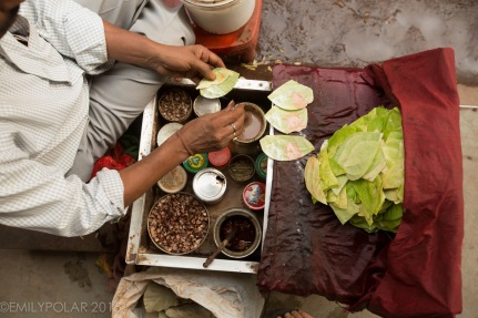 Indian man on the street preparing betel nut for customers in Old Delhi, India.