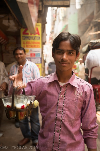 Young Indian boy carries chai holder to deliver to near by shops in the streets of Old Delhi.