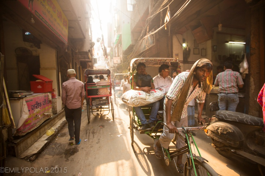 Indian rickshaw driver pulling two buisness men through narrow alley of Old Delhi.