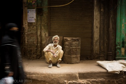 Indian man squatting on a curb in a busy alley of Old Delhi, India mixing his tobacco.