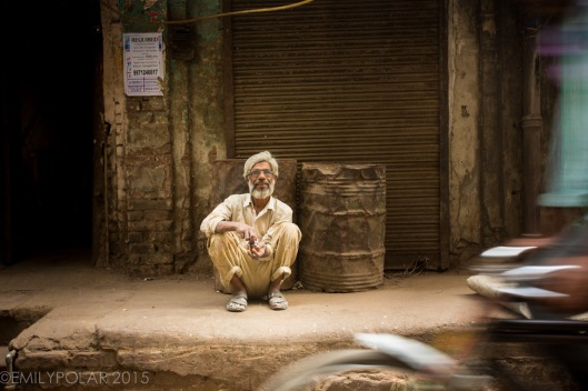 Indian man squatting on a curb in an alley of Old Delhi, India mixing his tobacco.