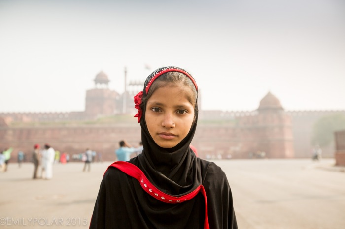 Young muslim girl looks at the camera with big brown eyes in Old Delhi, India.