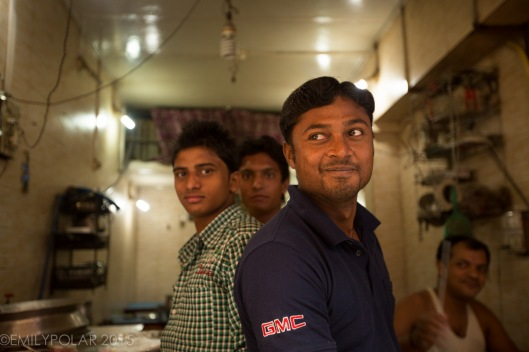 Cute Indian men pose for a picture while working at a street stall cooking food in Old Delhi, India.
