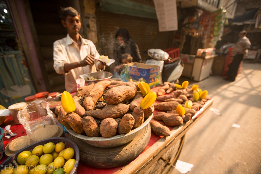 Indian man working at food stall serving up hot sweet potato in the streets of Old Delhi.