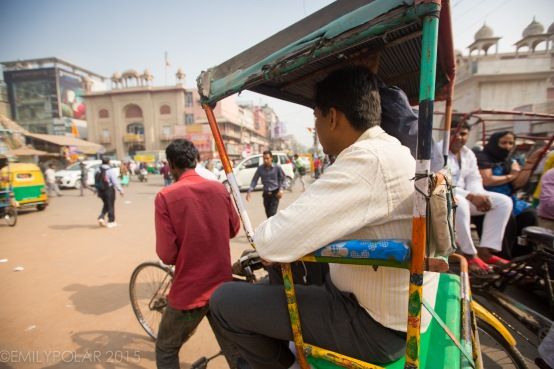 Indian man riding in the back of a rickshaw down the busy streets of Old Delhi, India.