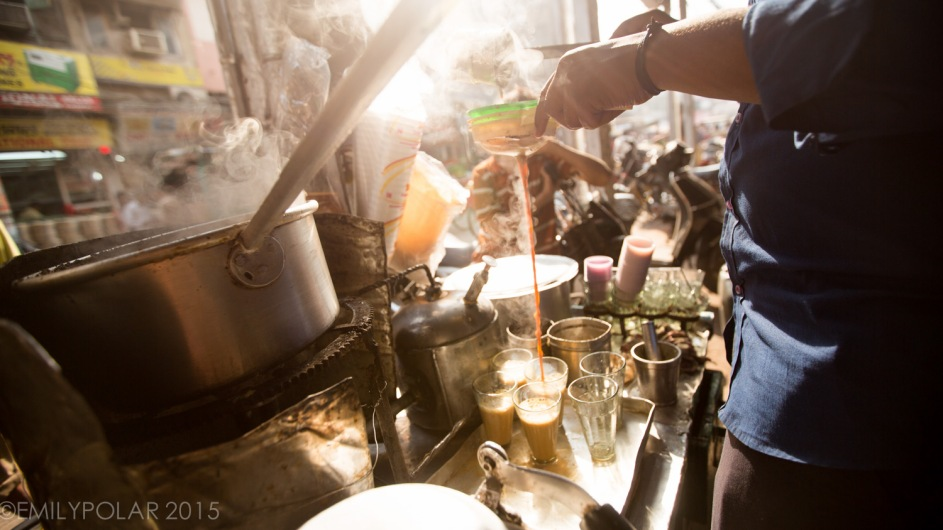 Indian boys making and selling chai at street cart in Old Delhi, India near Chawri Bazar.