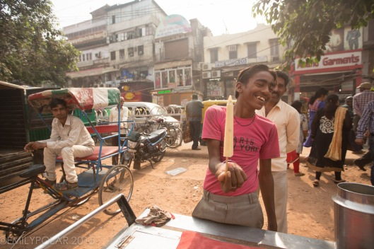 Young Indian boy working as a street food vendor selling frozen popsicle made from milk and sugar in Old Delhi, India.