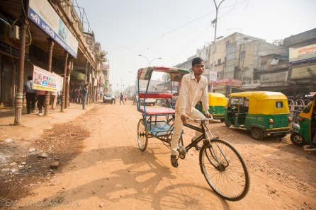 Indian man driving an empty rickshaw down a dirt street in Old Delhi, India.