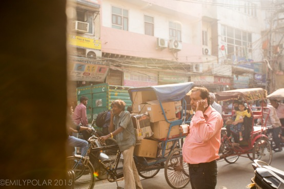 Indian man on phone drinking chai in the busy streets of Old Delhi, India near Chawri Bazar.