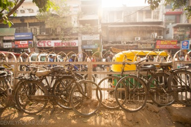 Stacks of old rusty bikes parked along metal fence in Old Delhi, India.