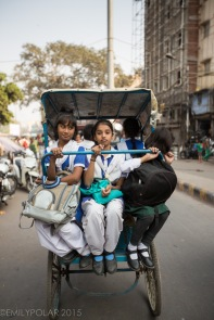 Young girls wearing school uniforms riding home in the back of a rickshaw in Old Delhi, India.