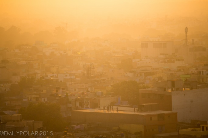 Warm glow of sunset casts a hue of orange through the haze of pollution over kids playing on the roof tops in Old Delhi India.