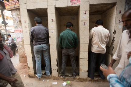 Indian men peeing at urinal in the street of Old Delhi, India.