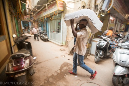 Men hauling stacks of paper and envelopes and cards from trucks to shops down alley ways in Chawri Bazar, Old Delhi.