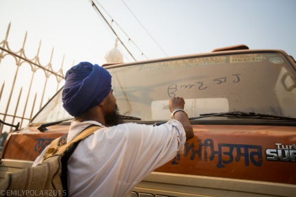 Sikh man drawing on the dusty windshield of a truck in the streets of Amritsar.