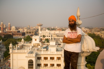 Portrait of a Punjabi Man in an orange turban and a T-shirt.
