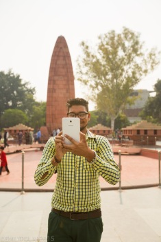 Indian man taking a photo with his huge smart phone at local monument in Amritsar.