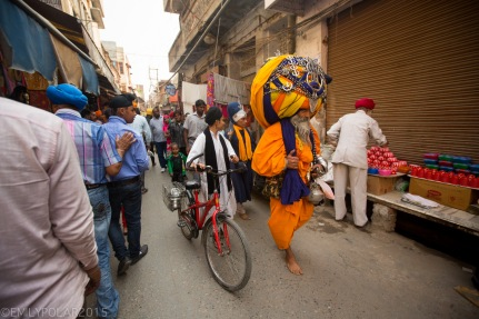 Sikh man walking down the street wearing huge turban with beard and sword dressed in orange and blue.