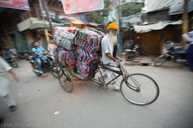 Cute Punjabi man pushes his tricycle loaded with fabric and textiles down a busy street in Amritsar.