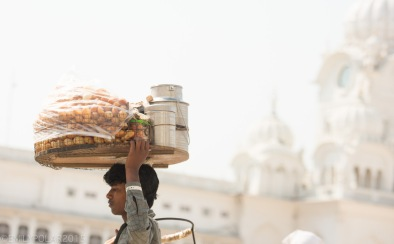 Young Indian boy carrying pani puri on his head around the clock tower at the Golden Temple.